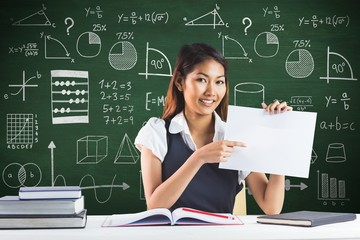 Composite image of smiling businesswoman pointing a sheet of