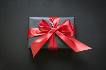Gift box wrapped in black paper with red ribbon on black surface.