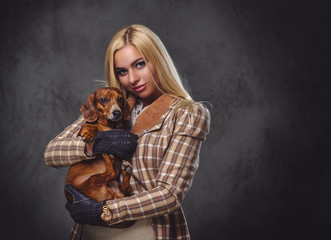 A stylish blonde female holds a red badger dog.