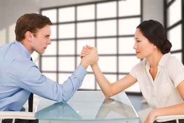 Composite image of business couple arm wrestling at desk