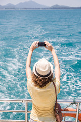 Female traveler taking pictures on a boat