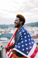 Happy black man holding an american flag standing on a rooftop.