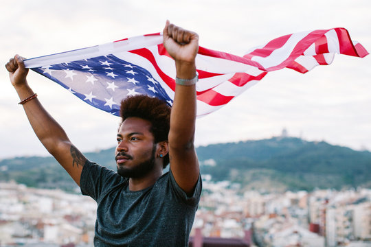Young black man waving an american flag outdoors.