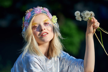 Young blond girl in sparkling hat with dandelions