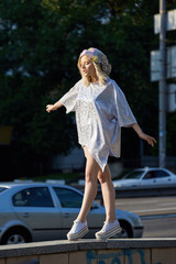 Young blond girl in sparkling hat walking on street