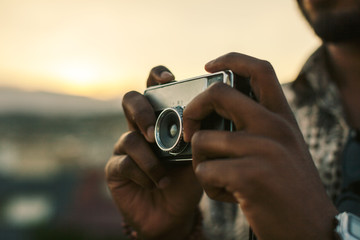Young black man taking a photo with an old camera at sunset.