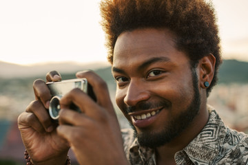 Young black man holding an old camera at sunset.