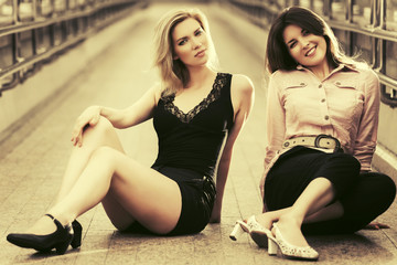 Two happy young fashion women sitting on the city sidewalk