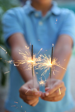Child holds 2 burning sparklers on the 4th of July