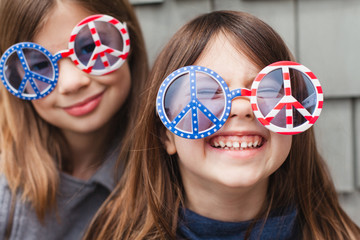 Silly sisters wearing patriotic peace sign glasses, United States of America