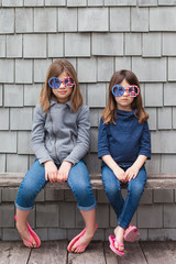 Solemn sisters wearing patriotic peace sign sunglasses