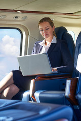 Businesswoman Working On Laptop In Helicopter Cabin During Flight