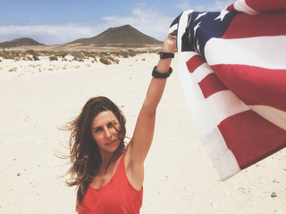 Pretty Woman With an American Flag in the Desert