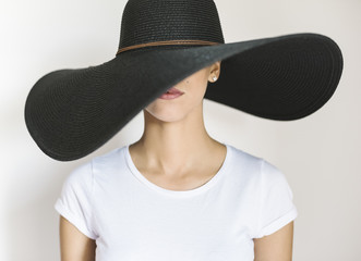 Young woman wearing a big black hat
