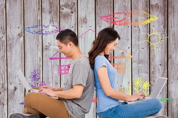 Composite image of happy young couple using laptop while sitting