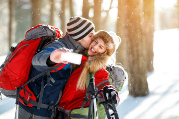 Young skiers kissing while making selfie