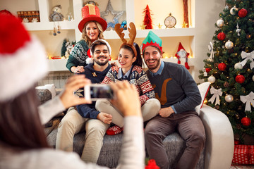 girl photographing friends by phone for Christmas.