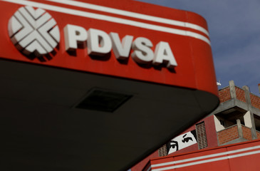 A painting depicting the eyes of Venezuela's late President Hugo Chavez, is pictured close to a corporate logo of the state oil company PDVSA at a gas station in Caracas