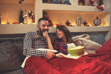 Christmas couple looking movie and eat popcorn in bed