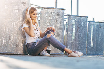 "Young smiling woman in a white T-shirt with word ""less"" listening music and sitting on the pavement"