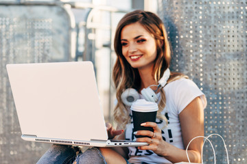 """Young woman in white T-shirt with word """"less"""" working for laptop and drinking coffee"""