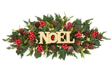 Christmas table decoration with gold noel sign, holly, ivy, mistletoe, fir and pine cones on white background.