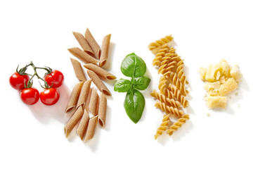 Penne and fusilli pasta, tomato, basil and cheese isolated on white background