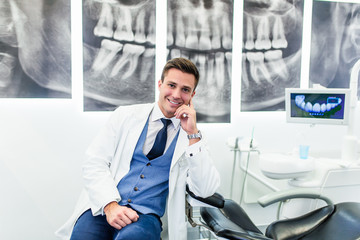 Portrait of handsome smiling dentist posing in his stomatology office.