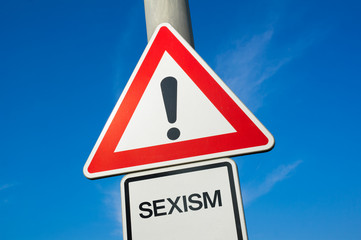 Sexism - traffic sign with exclamation mark to alert, warn caution - precaution and warning of violent and offensive attack and assault that is based on sex and gender