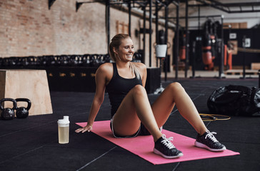 Smiling woman sitting on a gym floor after working out Wall mural