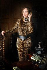 Woman in a leopard print dress with retro office