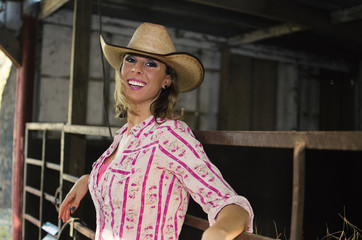 Western woman in cowboy hat wearing a smile in the barn.  Shows agriculture lifestyle with female.