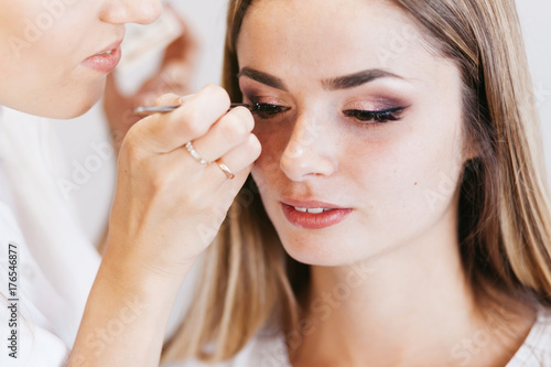 Professional Makeup Artist Working With Beautiful Young Woman In White T Shirt With Word