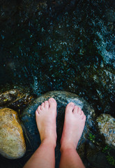 Barefooted close-up in a river full of stones