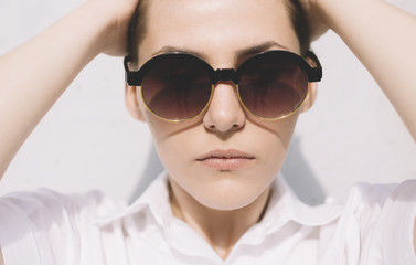 portrait of young woman with short hair and round sunglasses .
