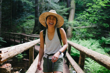 Woman laughing while crossing a bridge on a hike