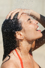 Portrait of a young woman washing under a shower on the beach.