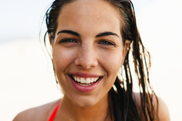 Portrait of a young brunette woman smiling standing on the beach.