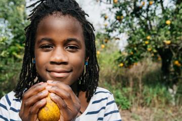 African American girl in an orange grove holding a ripened orange