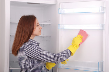Young girl cleaning empty fridge with a sponge.