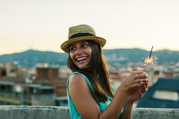 Happy young woman holding sparklers standing on a rooftop at sunset.