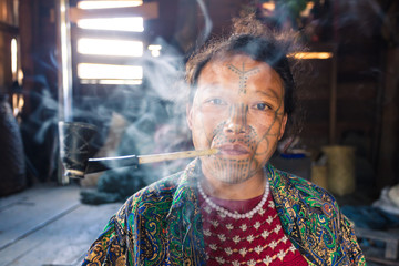 Chin woman with facial tattoo smoking pipe, Myanmar