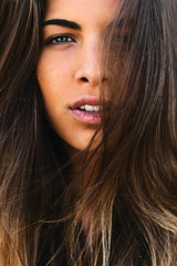 Closeup portrait of a young brunette woman with long hair looking at camera.