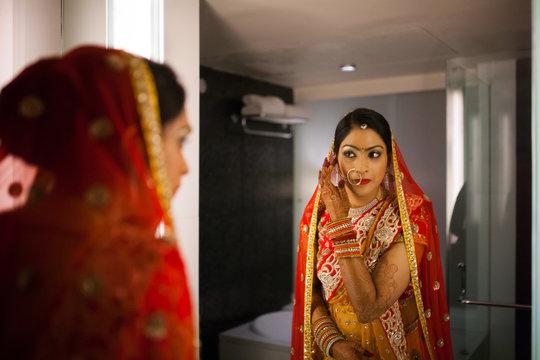 Bride preparing for wedding in front of mirror