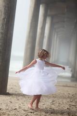 Girl Under Pier Twirling in White Dress