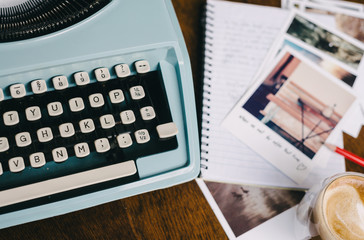 1960s vintage blue typewriter with notebook, photos and a coffee