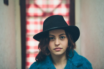 Portrait of a beautiful young woman wearing a hat in a corridor