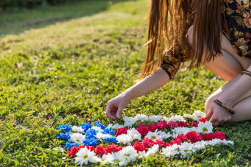 Young woman making an American flag out of flowers