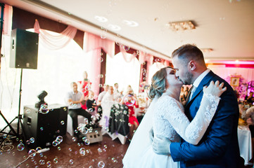 Beautiful wedding couple performing their first dance and kissing in the restaurant with different lights and bubbles and guests on the background.