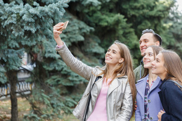 A group of smiling friends taking a mobile phone are photographed outdoors.